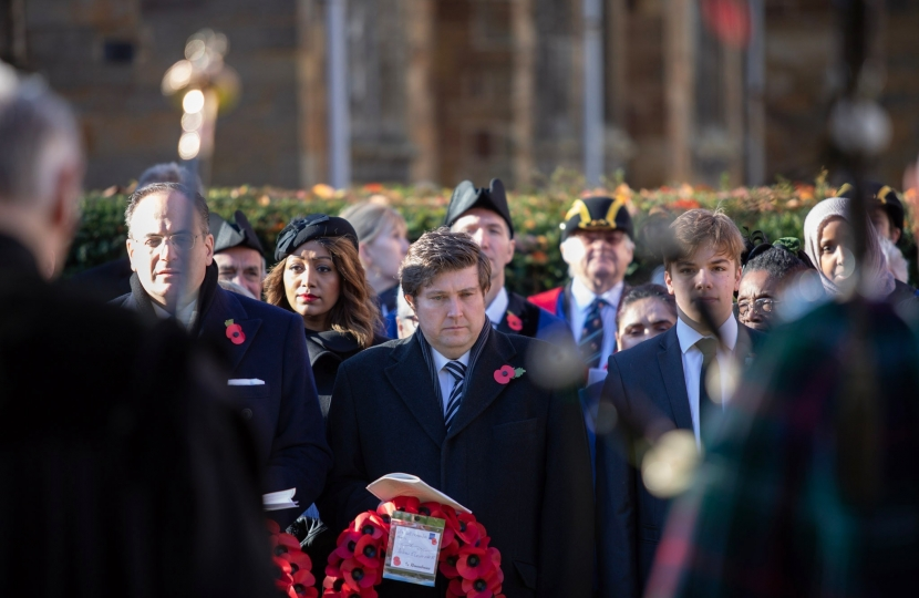 Andrew Lewer MP standing with his poppy wreath
